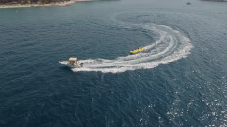 jet ski : Aerial view of inflatable towable banana tubes ride Stock Footage