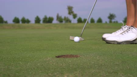 Man golfing and putting in hole. Male player on a golf course - Slider shot