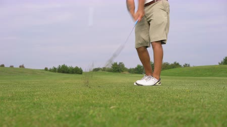 Male golf player on golf course, boom iron shot. Wide angle slider shot.