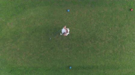 Aerial view of male golf player on golf course, boom driver shot.