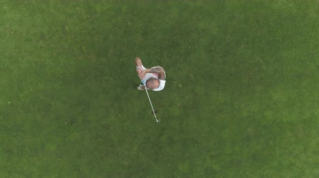 Aerial view of male golf player on golf course, boom iron shot.
