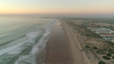 Aerial shot of ocean waves and beach at sunset. Aerial view of Ocean shore and resorts at sunset.
