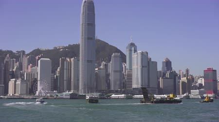 határkő : Hong Kong cityscape. Skyscrapers in financial district. Ferries at Victoria harbor - October 2018: Hong Kong, China Stock mozgókép