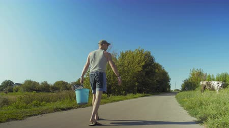 full bucket : Rural Man Carries A Bucket Of Water For Watering