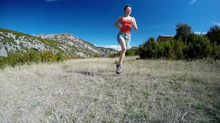 trilha : young woman running away on mountain trail in alpine pasture with mountain summits on the background