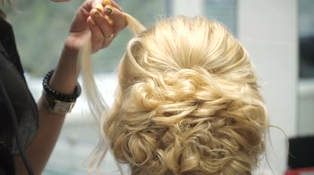 anelzinho : Portrait of a young woman in a beauty salon: creating a magnificent setting from curls. A blonde in a hairdresser does a beautiful hairstyle. Hair care and creating an image.