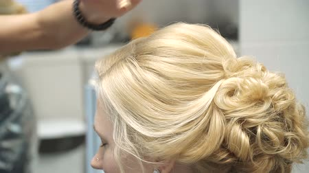 estilista : Portrait of a young woman in a beauty salon: creating a magnificent setting from curls. A blonde in a hairdresser does a beautiful hairstyle. Hair care and creating an image.