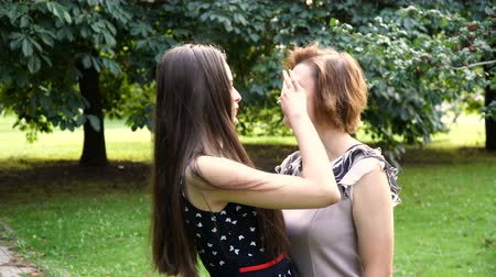 csók : Closeup Portrait of Adult Daughter and Mother Outdoors. Pretty Brunette and Her Mom are Looking at the Camera in the Park in Summer. Stock mozgókép