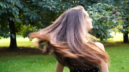emissão : Young, beautiful, attractive woman in a stylish dress, posing on camera. She laughs, poses for the camera, her hair blowing in the wind, looking very happy. slow motion