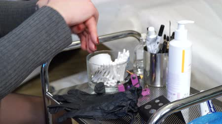 sanitize : specialist of permanent make-up disinfects hands before work.