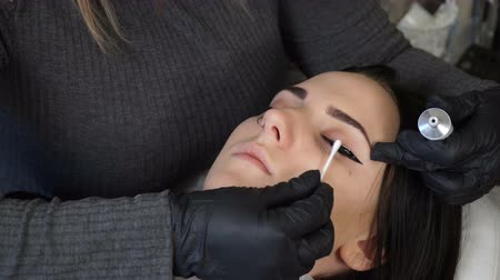 zalf : Beautician, specialist of permanent make-up is applying local anesthetic before the eye permanent makeup procedure. closeup. Stockvideo