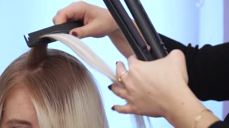гладильный : The hairdresser smoothes the hair of a beautiful young girl. hair straightening Стоковые видеозаписи
