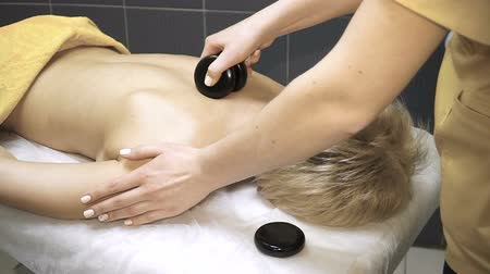 コチョウラン : Young woman enjoying a hot massage in a spa salon as heat basalt stones are placed on her muscles 動画素材