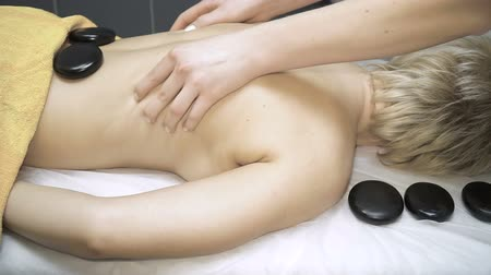 orchidea : Young woman enjoying a hot massage in a spa salon as heat basalt stones are placed on her muscles Wideo