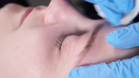 pomada : Beautician, specialist of permanent make-up is applying local anesthetic before the eyebrows permanent makeup procedure. closeup.