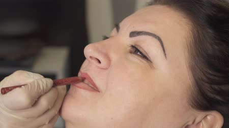 permanente : Close up shot. Professional specialist of permanent make-up applying lips before the procedure. Beauty, makeup and fashion concept Filmati Stock