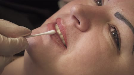 zalf : Beautician, specialist of permanent make-up is applying local anesthetic before the lips permanent makeup procedure. closeup.