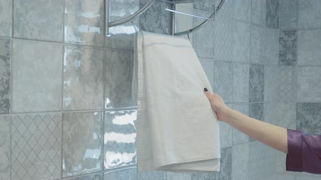 material body : A womans hand takes the towel. the white towel weighs on the dryer