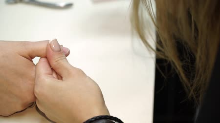 vernik : Closeup shot of a woman in a nail salon receiving a manicure by a beautician with nail file. Woman getting nail manicure. Beautician file nails to a customer