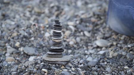 stapelen : The man is building the balancing stone tower on the beach Stockvideo