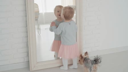 first person : Beautiful little girl stay near the mirror with dog. Slow Motion. Baby milestone, toddler, 1 year old. Happy childhood