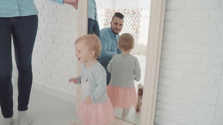 choise : Beautiful little girl stay near the mirror with her family and dog. Slow Motion. Baby milestone, toddler, 1 year old. Happy childhood