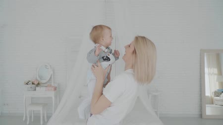 otcovství : Mother swinging her beautiful daughter in the room. Happy family. Slow motion