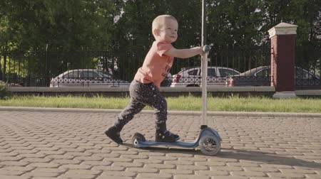 robogó : little lovely boy on the kick scooter in the park. Slow motion