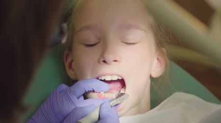 só : Young girl having her teeth fixed at the dentists. Caries cleanup. The dentist brushes his teeth with an electric toothbrush