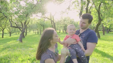 bond : Happy young parents share kiss their cute baby boy outdoors in park. Slow motion Stockvideo
