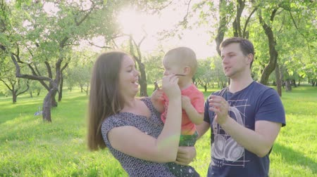 çim : Happy young parents share kiss their cute baby boy outdoors in park. Slow motion Stok Video