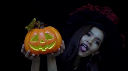 salva : Playful woman in Halloween costume hiding and showing funny face behind Halloween pumpkin or Jack O Lantern