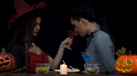 martini glasses : Couple in Halloween costume celebrating with glass of liquor in Halloween night party