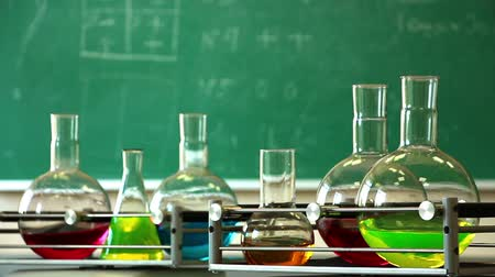 skvrny : Six glass flasks filled with solutions of different colors synchronously rotate on the laboratory shakers platforms on the green chalkboard background. Focus on right front platform. No camera movement. Close up.
