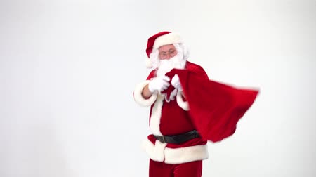 çuval : Christmas. Santa Claus on a white background takes out a red box with a bow from a bag, gives it. Present. Surprise. Stok Video