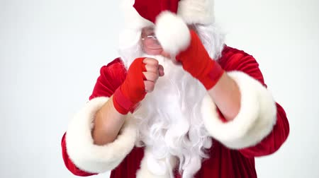 kendi : Christmas. Santa Claus on a white background in red bows for boxing and kickboxing fulfills blows. The image of a fighter. Humor, funny, fun, joke, has its own bumbon.