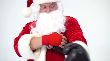 alkalom : Christmas. Santa Claus on a white background wears black boxing gloves and fulfills punches. Kickboxing, fighter. Wears gloves on red bandages.