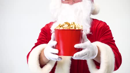 çuval : Santa Claus on a white background with a red bucket of popcorn. Eats popcorn and watches a movie, offers popcorn. Stok Video