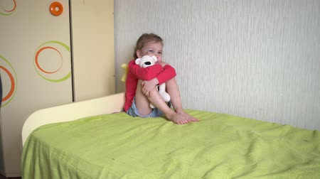 ameaça : Domestic violence. The father threatens the child with a belt. Sad girl with a black eye sitting on the bed, holding a toy bear and closes his eyes with his hands. Fear.