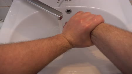 unclog : Clogged sink pipe. A man washes his hands in the sink. Close up. Shows that everything is good. Like. The blockage is removed.