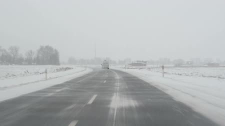 kar fırtınası : cars going on winter rural road and blizzard snow fall carried by strong wind.