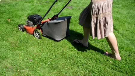 yards : walk woman girl in skirt and flip-flop shoes cut lawn grass mower in yard. Stock Footage