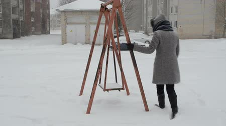 kar fırtınası : woman with coat sit on old retro steel swing. winterstorm blizzard snow fall.  Stok Video