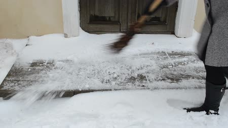 career path : woman worker sweeper clean broom gobble snow from tiles near house door entrance.   Stock Footage