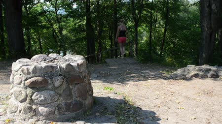 шорты : young sexy woman in shorts pass old stone pagan altar climb down stairs hill Стоковые видеозаписи