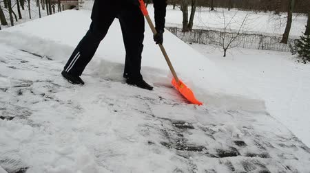 deep snow : man in black with plastic orange shovel tool push clean snow from roof in winter.