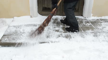 cleaning equipment : man worker sweeper clean broom gobble snow from tiles near house door.