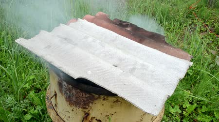 strawberry oil : smoke rises from old rural handmade barrel smokehouse slate roof.
