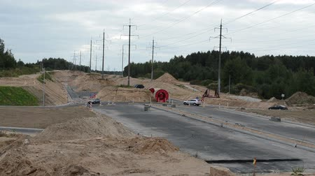 ayrıntılar : cars go round roundabout and new highway construction site and high voltage electricity poles wires.