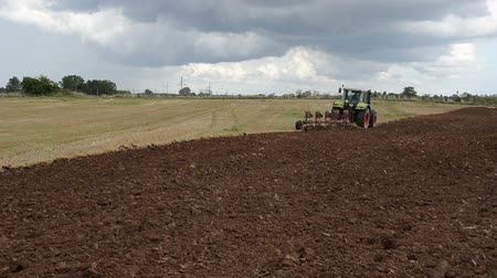 arado : heavy agriculture machine tractor plow field in august. Stock Footage